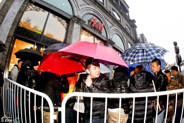 Shoppers queue in the rain before the launch of the Versace for H&M collection outside an H&M store in Beijing