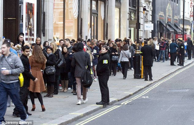 Hordes: Security guards attempted to keep the ever-growing queues under control as more and more shoppers joined the line
