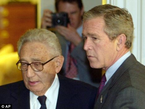Still on duty: Mr Kissinger and George W Bush in the White House in 2002, ahead of Mr Bush signing legislation for a commission into the 9/11 attacks