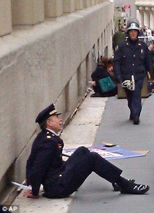 Retired Philadelphia Police Captain Ray Lewis, left, sits on the ground handcuffed after being arrested in New York near Wall Street during an Occupy Wall Street protest, Thursday, Nov. 17, 2011