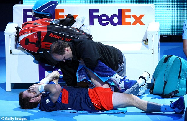 Pain game: Murray receives treatment midway through the match