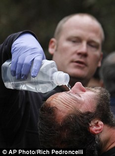 University of California, Davis, student Mike Fetterman, receives a  treatment for pepper spray by UC Davis firefighter Nate Potter on Friday, Nov. 18, 2011.