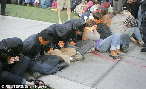 """University of California Davis students covered in pepper spray sit during an """"Occupy UCD"""" demonstration in Davis, California November 18, 2011."""