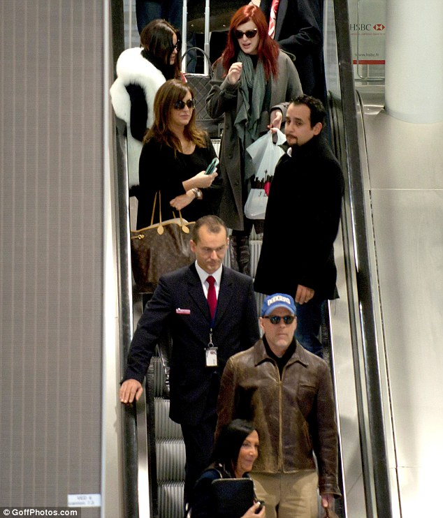 On the move: The family take the escalator as they make their way through the airport