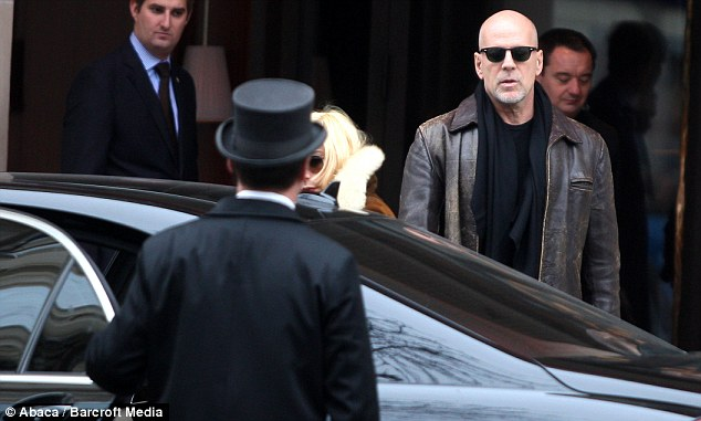 Daughter day out: Bruce waits outside his hotel as newly blonde Talullah gets into the car