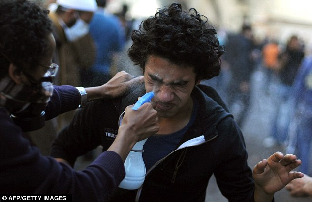 Tear gas: An Egyptian protester sprays water on the eyes of a fellow demonstrator after tear gas was fired by security forces firing tear gas in Tahrir Square in Cairo