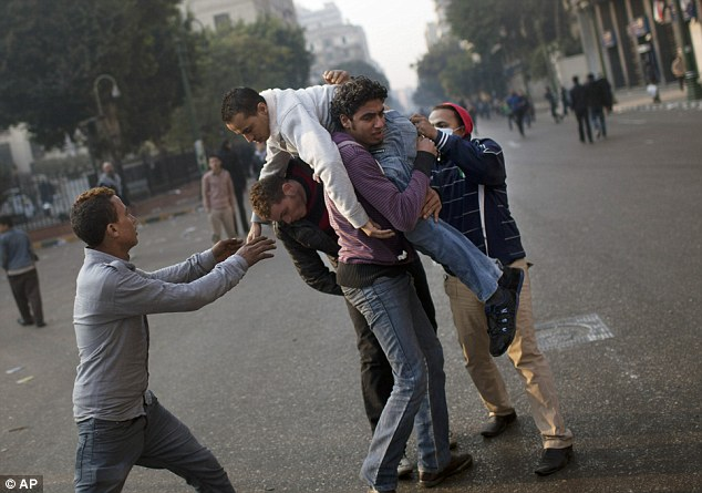 Casualties: An injured protester is aided by others during clashes with Egyptian security forces, not pictured, near Tahrir Square in Cairo