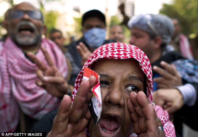 Voices to be heard: An Egyptian demonstrator shouts slogans at a protest camp outside the prime minister's office in Cairo as part of ongoing demonstrations calling for an end to the military rule