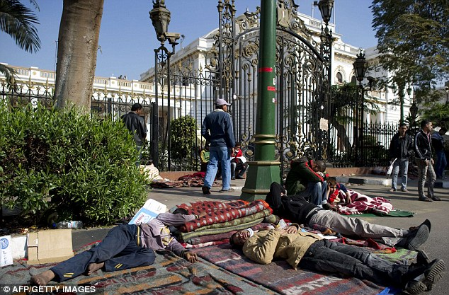 Downtime: Egyptian demonstrators sleep at a protest camp set up overnight outside the prime minister's office in Cairo as part of ongoing demonstrations