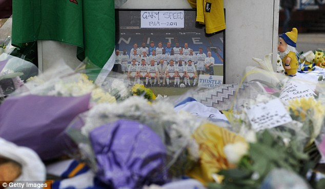 Tributes: Hundreds of tributes including photographs, shirts and bouquets of flowers have been left at the Elland Road ground