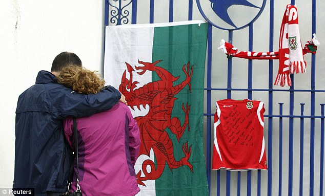 Cardiff City: A couple embrace as they look at tributes to Wales manager Gary Speed left outside Cardiff's ground