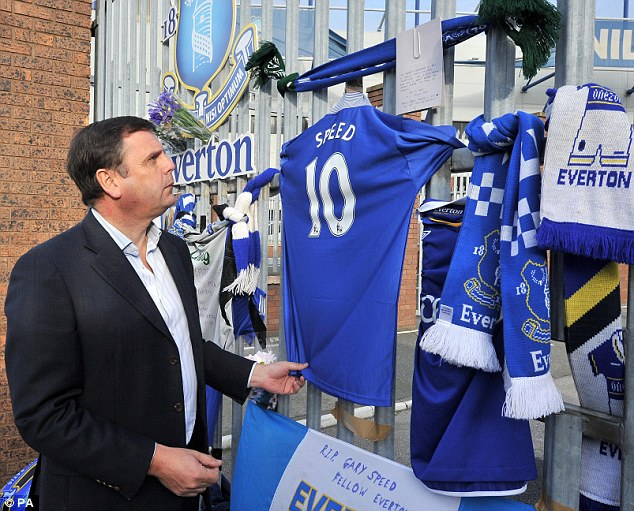 Paying his respects: Former Everton player Graeme Sharp looks at tributes left outside the gates to Goodison Park