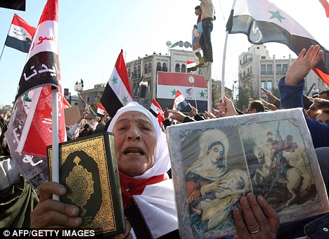 Support for the regime: A Syrian woman holds up a copy of the Muslim Koran next to a Christian icons, during a rally against sanctions imposed against by the Arab League