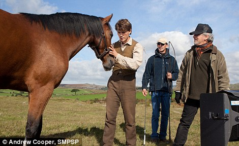 Up close: Actor Jeremy Irvine, left, with members of the crew during rehearsals
