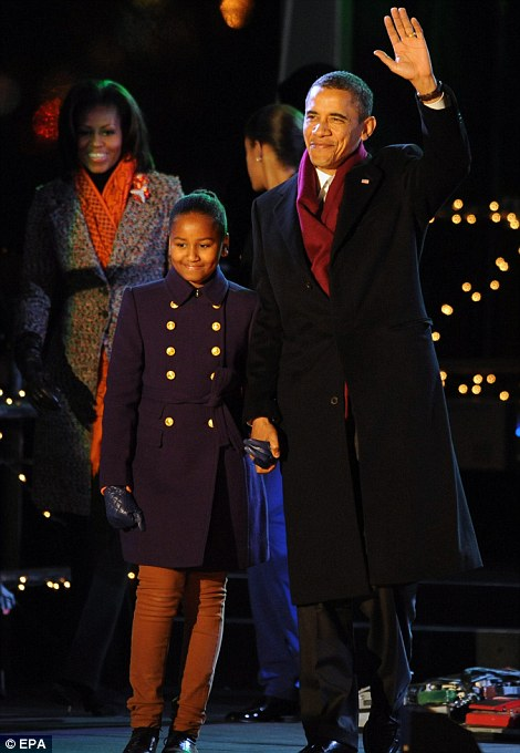 Seasons greetings: US President Barack Obama greets a crowd with his daughter Sasha (front left) and First Lady Michelle Obama (back left), during the 89th annual lighting of the National Christmas Tree