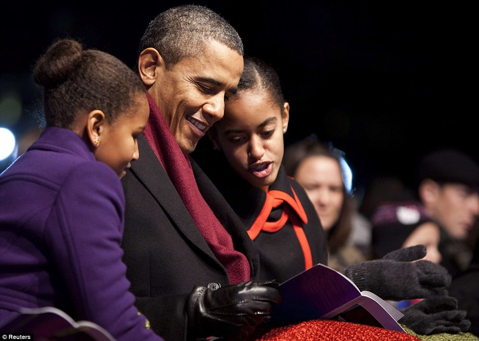 So much to see: President Obama and his daughters Sasha (left) and Malia (right) look at the program during the lighting of the National Christmas Tree