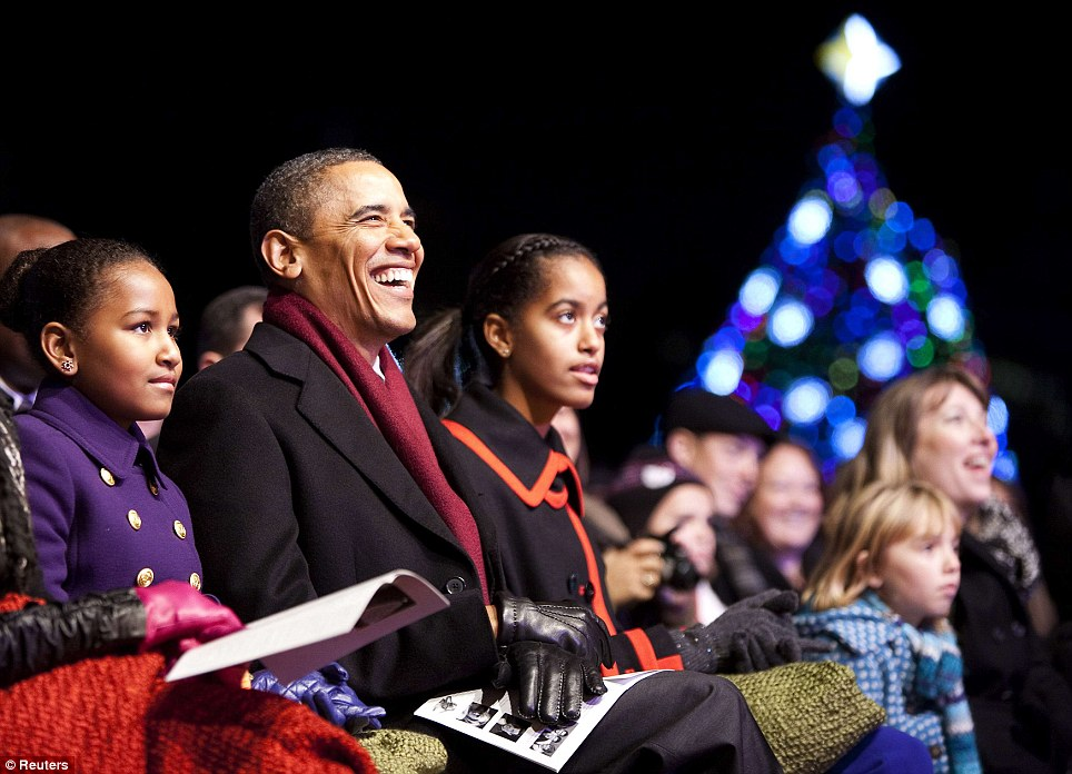 Big smiles: Mr Obama laughs as he enjoys the show with daughters Sasha (left) and Malia (right)