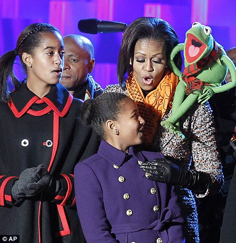 First Family: Mrs Obama sings with daughters Malia (left) and Sasha (centre), and Kermit the Frog, while Mr Obama sings with Santa Claus during the 2011 National Christmas Tree Lighting ceremony