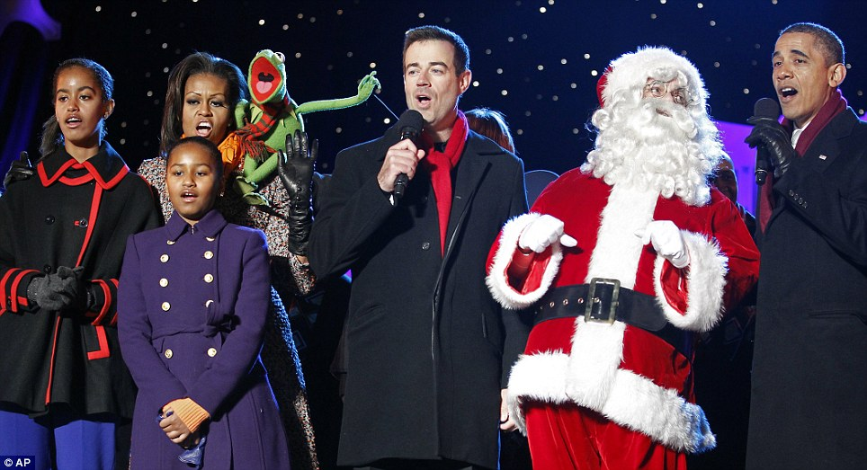Carolling: President Barack Obama, First Lady Michelle Obama and their daughters Sasha and Malia sing along with Carson Daly and Kermit the Frog during the annual National Christmas Tree Lighting on the Ellipse today