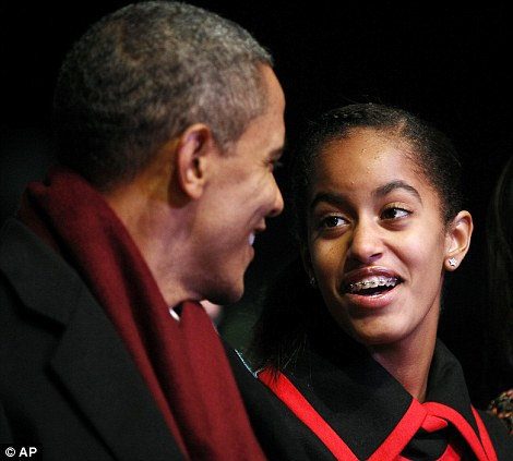 Making memories: Mr Obama and his daughters Malia (left) and Sasha (right) laugh together during the ceremony