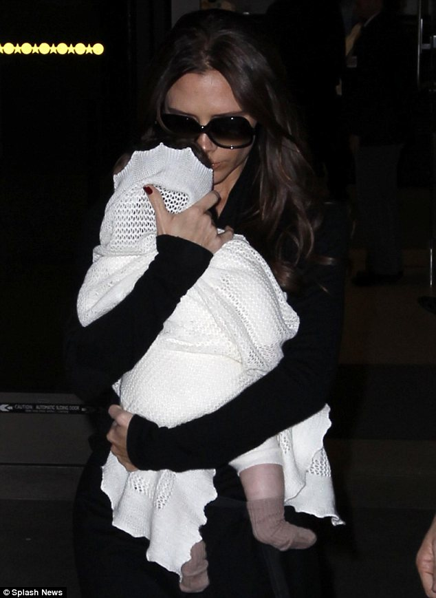 Babe in arms: Victoria Beckham was seen cuddling Harper as they landed at LAX on Thursday
