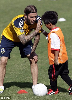 Fatherly instincts: David Beckham high-fives children while conducting a football clinic at the Rizal Memorial Football Stadium in Manila, Philippines