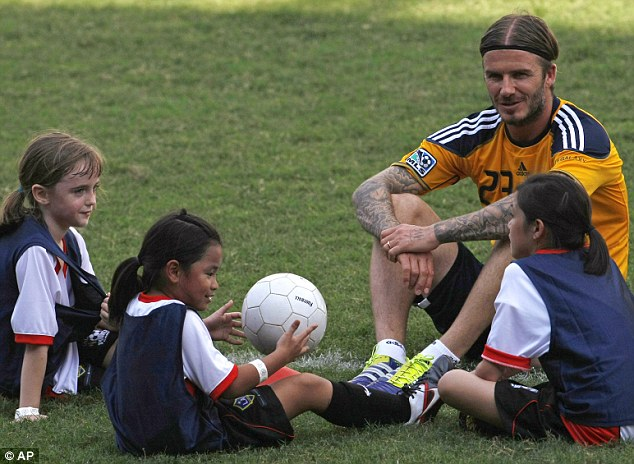 One of the girls: Footballer chatters to a group of children as they take a break from playing sport