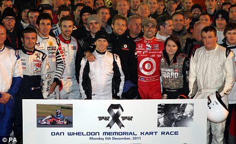 Fitting tribute: Jenson Button (centre) joins fellow racing drivers at the Dan Wheldon Memorial Kart Race in Milton Keynes on Monday night and (below) takes to the track in his kart