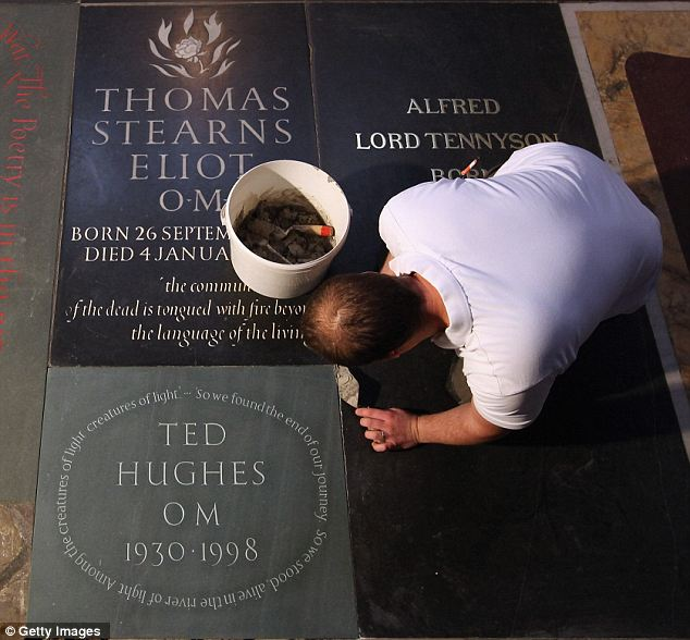 A stonemason puts the finishing touches to a new memorial to Ted Hughes, the former Poet Laureate, in Poets' Corner inside Westminster Abbey last night