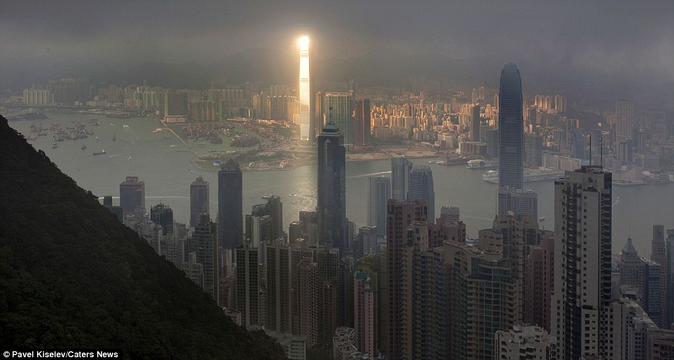 Freak of nature: This is the spectacular moment a bright beam of sunlight illuminated the International Commerce Centre in West Kowloon, Hong Kong