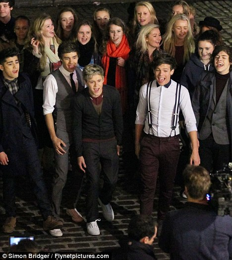Babe magnets: One Direction were swamped by female fans on the set of their latest video - and eventually let the girls take part in filming