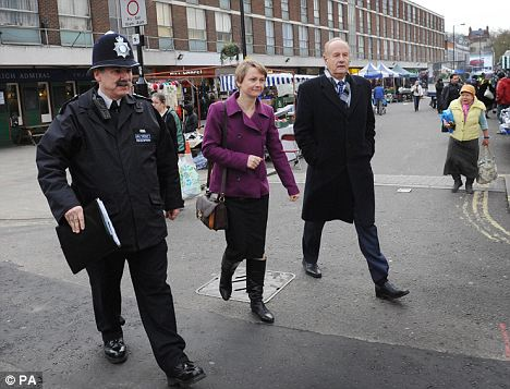 Lord Stevens, right, with Yvette Cooper. She warned that British officers face a 'perfect storm' of cuts in staff, 'chaotic' reforms and evolving threats to the public
