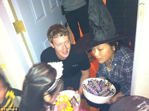 Trick of treat: He kneels with his girlfriend who holds a bowl of Snickers and other chocolate bars on Halloween