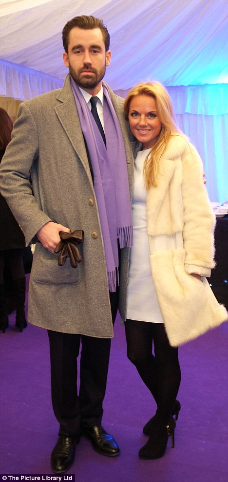Cosy: Louis puts an arm around Geri as they pose inside on the purple carpet