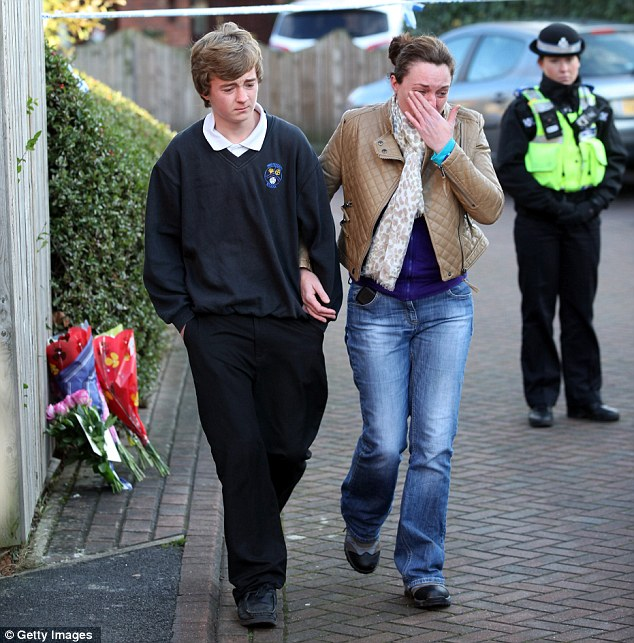 Family friend Sarah Wilson and an unidentified youth leave after placing flowers near the house