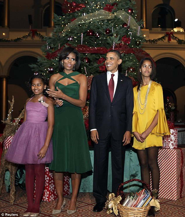 Looking festive: The Obama family gather under the Christmas tree as they attend the 30th fundraising carol concert in the capital