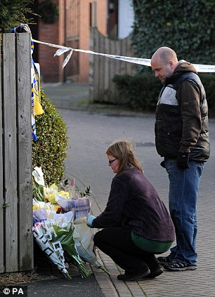 Members of the public lay flowers at the police cordon in Pudsey, Leeds