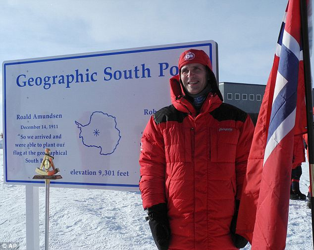 Mr Stoltenberg stands next to  a sign marking the geographical South Pole on Monday, after he flew to the spot in advance of the centenary