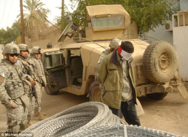 Troubled country: A suspected insurgent is led away by a patrol