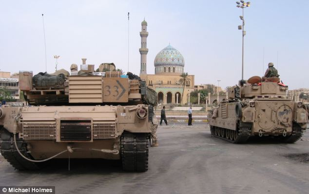 Constant vigilance: A U.S. Abrams tank and an armoured personnel carrier on guard outside the Palestine Hotel, facing Baghdad's Firdos Square, where Saddam's statue was pulled down