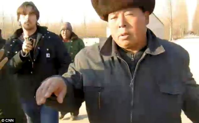 Raising awareness: Christian Bale continues filming as the guard attempts to shove the CNN crew in the scuffle in the Dongshigu village