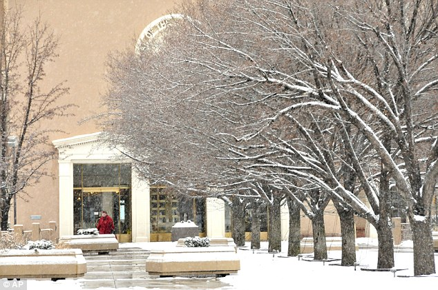 Picture postcard: Snow covered trees make for a scenic view of the east entrance to the Santa Fe New Mexico state capitol as residents deal with the winter storm that hit on Monday