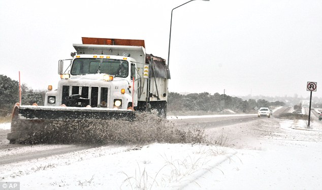 Clearance: Snow plow clears snow from Old Pecos Trail in Santa Fe, New Mexico, on Monday, as local residents deal with a winter storm. State police say a winter storm is shutting highways