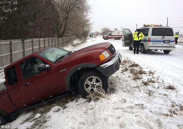 Stuck: Longmont police respond to three separate weather-related accidents as snow falls on Colorado Highway 66 in Longmont, Colorado, on Monday. A major storm is bringing blizzard conditions to the U.S.