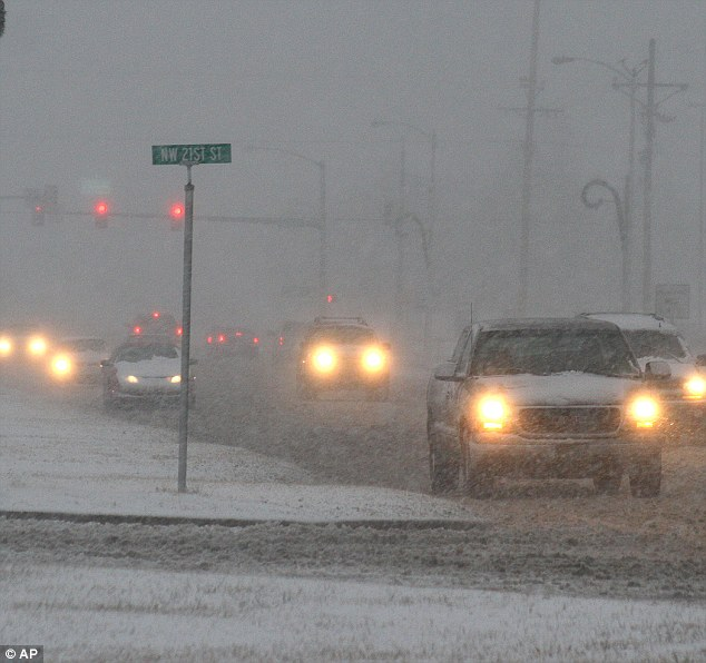 Limited visibility: Traffic makes its way down Highway 64 as snow and sleet falls on Monday in Guymon, Oklahoma. The wintry weather was preceded by more than a half-inch of rain and a blizzard warning is in effect