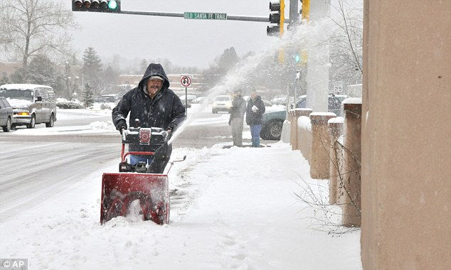 The big chill: The snow blowers were out clearing sidewalks in Santa Fe as dusk began to fall on Monday
