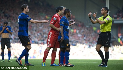 Man in the middle: Ref Andre Marriner had to speak to Evra and Suarez at Anfield
