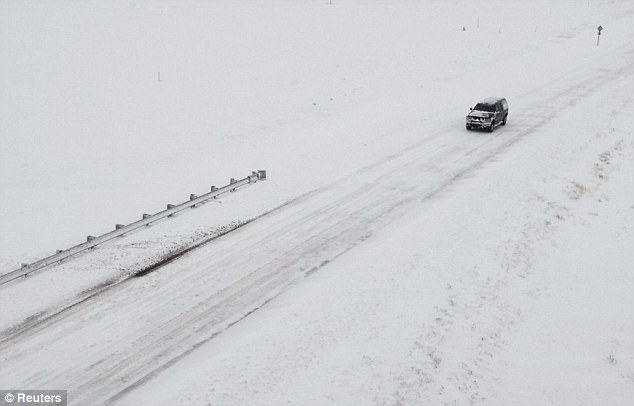 Lonely: A truck travels along Highway 40 as snow covers the highway and the surrounding plains, west of Hays, Kansas, on Tuesday