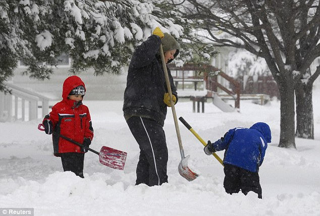 Fun with mum: Cindy Gaschler, centre, gets help from her two sons Eric, left, and Ethan, right, as they dig out in Ellis, Kansas, after a winter storm on Tuesday