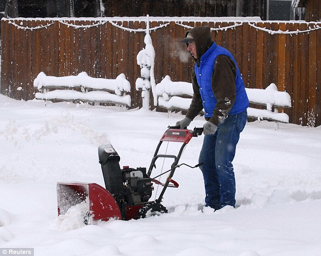 Chilly: Al Ashmore uses a snow blower to dig out on in Hays, Kansas, on Monday. A blizzard shut down highways in New Mexico, Colorado, Kansas and the panhandles of Oklahoma and Texas on Monday
